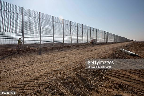Israeli workers erect a new fence along Israel's border with Jordan in the Arabah valley some 30 Kilometres north to the southern Israeli resort city...
