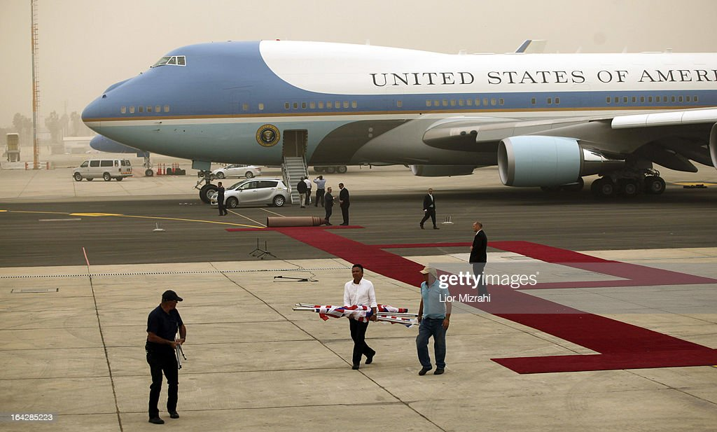 Israeli workers remove U.S. and Israeli flags from the tarmac during a wind storm prior to U.S. President Barak Obama departing from Ben Gurion International Airport on March 22, 2013 in Lod' Israel. Obama concluded his first visit to Israel and West Bank after three-days of meetings with Israeli and Palestinian leaders.