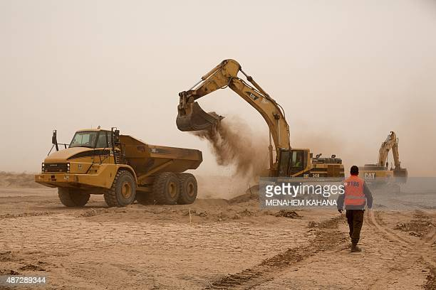Israeli workers use excavators at the construction site of a new fence along Israel's border with Jordan in the Arabah valley some 30 Kilometres...