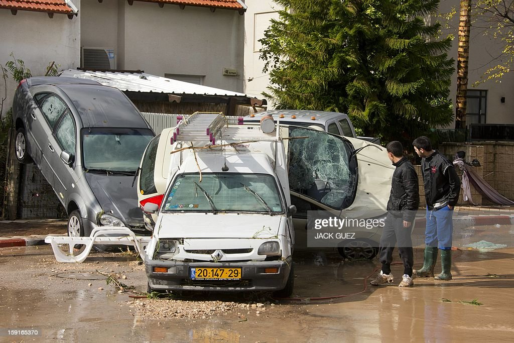 Israeli youths look at damaged cars in Beit Hefer near the Mediterranean coastal city of Netanya, north of Tel Aviv, on January 9, 2013, after heavy rains overnight. Israel and the Palestinian territories have been lashed by heavy rain and high winds since January 6, which has caused flooding across the region. AFP PHOTO / JACK GUEZ