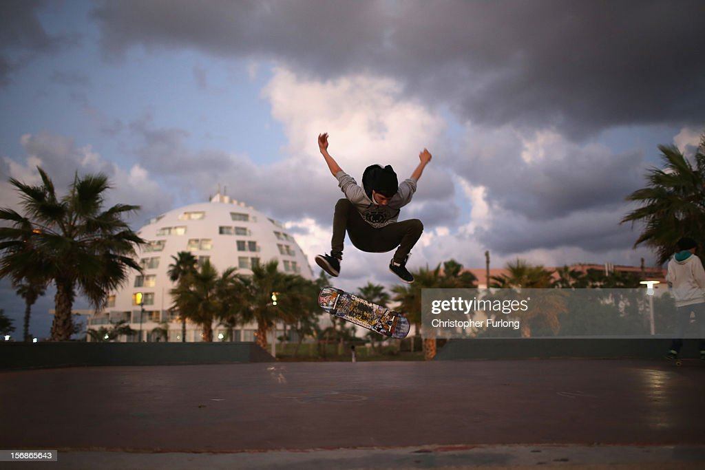 Israeli youths practice their skate boarding skills near the beach in the southern Israeli town of Ashkelon on November 23, 2012 in Ashkelon, Israel. Daily life in the southern border towns of Israel are returning to normal after eight days of rockets and alerts during the recent conflict between Israel and Hamas militants in the Gaza Strip.