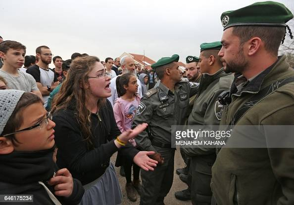 Israeli youths supporters of settlements argue with Israeli border guards in the settlement of Ofra in the occupied West Bank during an operation by...