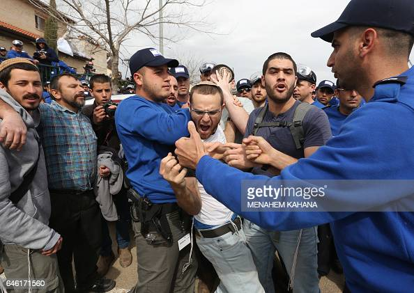 Israeli youths supporters of settlements argue with Israeli police forces near a house which is due to be emptied and demolished in the settlement of...