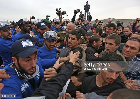 Israeli youths supporters of settlements argue with Israeli police forces in the settlement of Ofra in the occupied West Bank during an operation to...