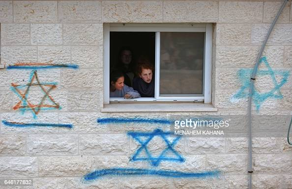 TOPSHOT Israeli youths supporters of settlements gather inside a house in the settlement of Ofra in the occupied West Bank during an operation by...