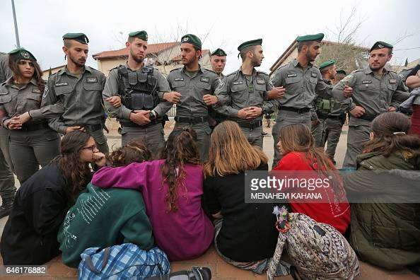 Israeli youths supporters of settlements hug near Israeli border guards in the settlement of Ofra in the occupied West Bank during an operation by...