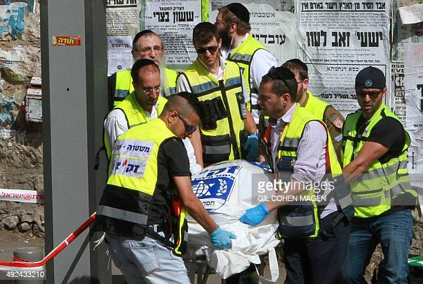 Israeli Zaka volunteers carry the body of an Israeli victim after a Palestinian man drove into a bus stop and carried out a stabbing attack in a...