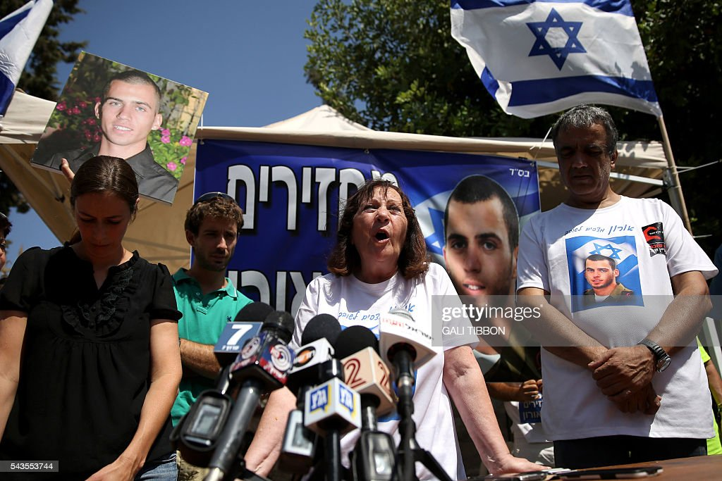 Israeli Zehava Shaul, the mother of slain Israeli soldier Oron Shaul, who was killed in Gaza during the summer of 2014's 50-day military campaign against Hamas and body's has not been recovered, speaks during a press conference on June 29, 2016 next to her husband Herzel (R) at their protest tent outside thr prime minister's residence in Jerusalem. Zur (L) and Ayelet Goldin whose brother Israeli army Lt. Hadar Goldin was also killed in Gaza and his body is believed to be held by Hamas, are also seen in the picture. The Israeli army believes they were killed and Hamas has yet to provide reliable evidence to counter that. TIBBON