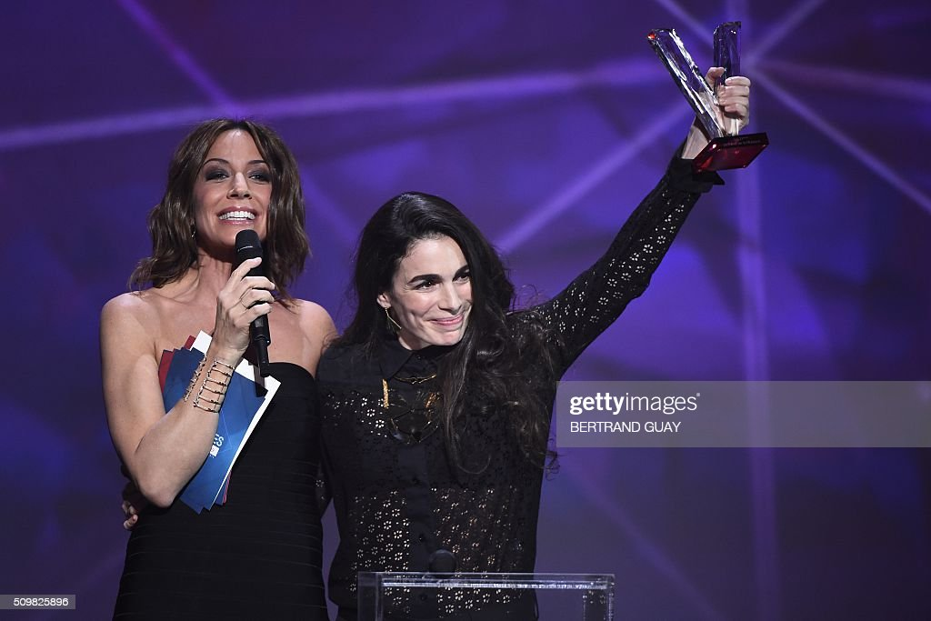 Israeli-French singer-songwriter Yael Naim (R), flanked by French TV host and Master of Ceremony Virginie Guilhaume (L) gestures after receiving the female artist award during the 31st Victoires de la Musique, the annual French music awards ceremony, on February 12, 2016 at the Zenith concert hall in Paris. AFP PHOTO / BERTRAND GUAY / AFP / BERTRAND GUAY