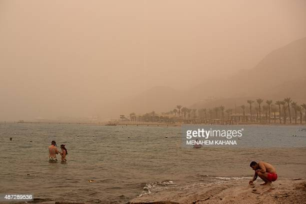 Israelis and tourists take a dip in the red sea in the southern Israeli coastal city of Eilat on September 8 as a sandstorm engulfs parts of the...