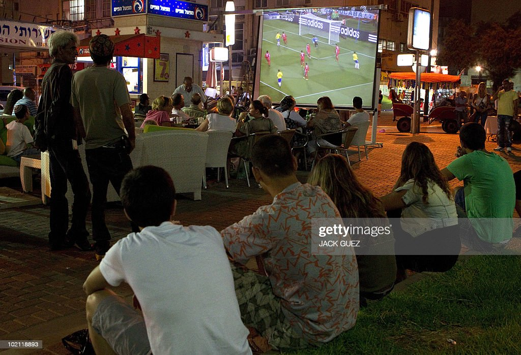 Israelis and tourists watch on a big screen the 2010 World Cup football match between Brazil and North Korea at a restaurant in the costal city of Netanya on June 15, 2010.