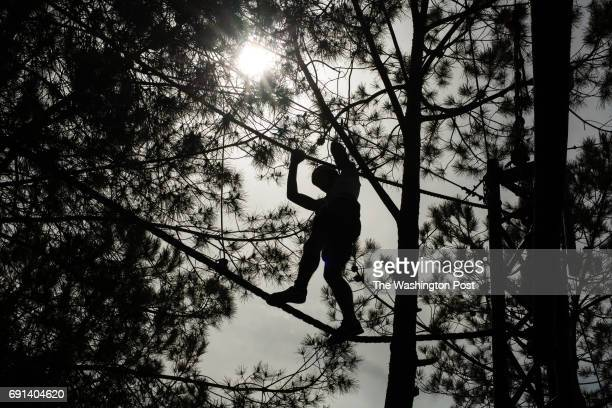 Israelis are silhouetted as they climb a high ropes course at Deer Land Farm near the West Bank Jewish settlement of Alon Shvut in the Gush Etzion...