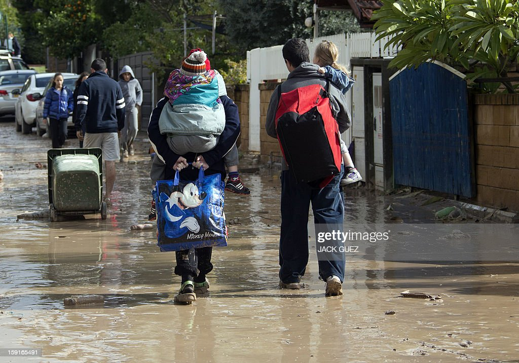 Israelis carry their children as they walk through muddy streets due to heavy rains overnight that caused flooding in Beit Hefer, near the Mediterranean coastal city of Netanya, north of Tel Aviv, on January 9, 2013. Israel and the Palestinian territories have been lashed by heavy rain and high winds since January 6, which has caused flooding across the region. AFP PHOTO / JACK GUEZ