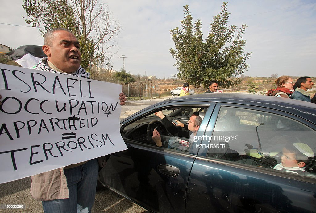 Israelis drive past a Palestinian protester holding a banner during a protest against the Israeli occupation on the main road 60 between the West Bank cities of Bethlehem and Hebron near the Israeli settlement of Daniel on January 25, 2013.