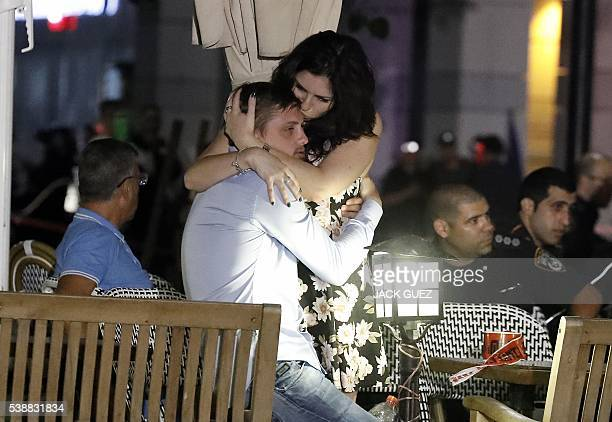 TOPSHOT Israelis embrace following a shooting attack at a shopping complex in the Mediterranean coastal city of Tel Aviv on June 8 2016 At least...