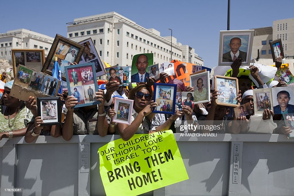 Israelis from the Ethiopian community hold photographs of their relatives outside Prime Minister Benjamin Netanyahu's office in Jerusalem on August 28, 2013 during a demonstration calling the government to bring thousands of their loved one from Ethiopia to Israel.