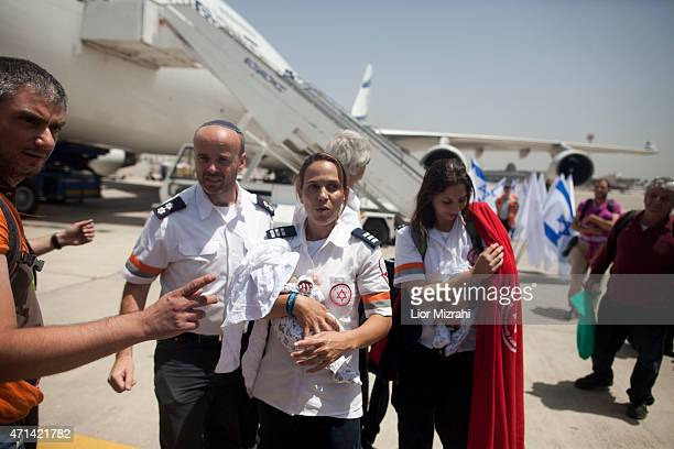 Israelis from the Israeli rescue organization Magen David Adom hold babies from surrogate mothers in Nepal after they disembark from an Israeli...