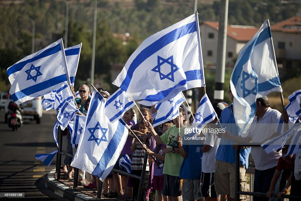 Israelis hold Israeli flags along the road of the funeral procession of Gilad Shaer on July 1 2014 in Hashmonaim settelment West Bank The bodies of...