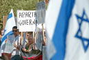 Israelis hold signs as they demonstrate against what they call an 'Apartheid Government' outside Prime Minister Ariel Sharon's offices during the...