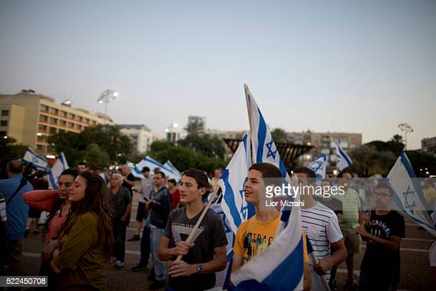 Israelis hold up flags during a rally in support of Israeli soldier Elor Azaria on April 19 2016 in Tel Aviv Israel Sergeant Azaria was charged on...