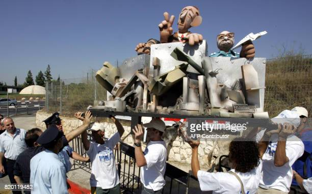 Israelis holding up a platform with effigies of Defence Minister Amir Peretz Prime Minister Ehud Olmert and Chief of Staff Dan Halutz protest outside...