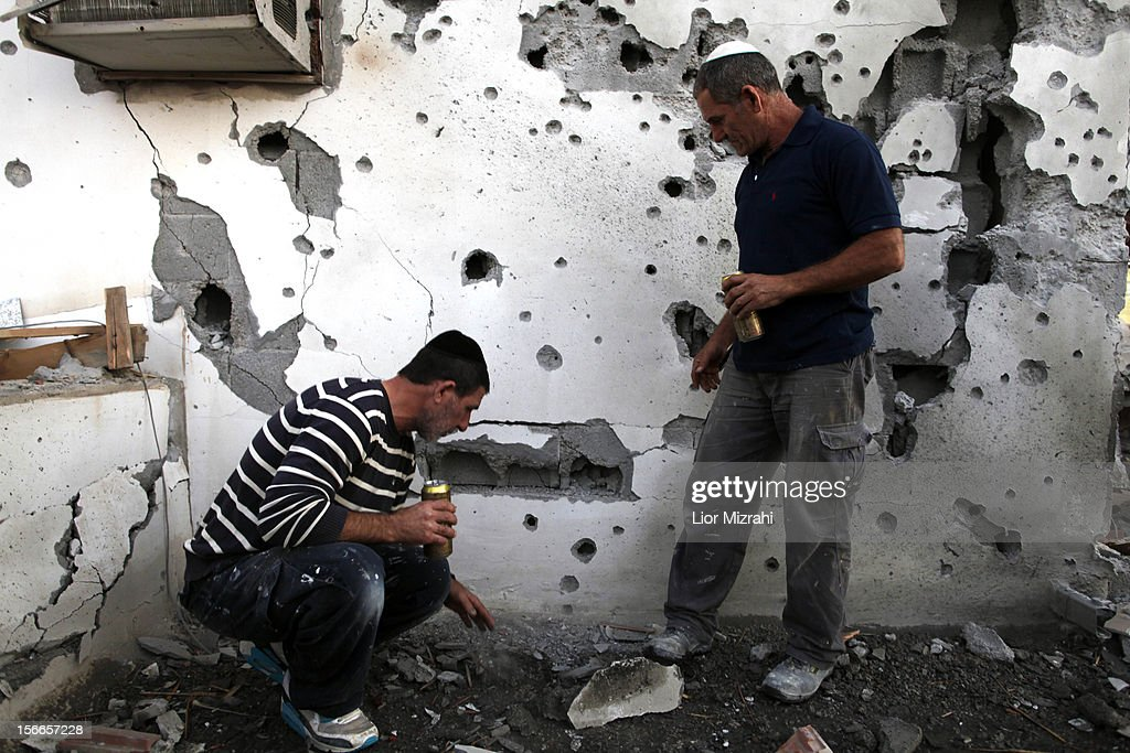 Israelis inspect the damage to a house that was hit by a rocket fired by Palestinian militants from the Gaza Strip on November 18, 2012 in Ofakim, Israel. Israeli/Gaza attacks have entered the fifth day, with two media buildings being recently struck and several journalists subsequently injured. According to health officials in Gaza, at least 50 Palestinians have been killed since Israel launched operation Pillar of Defence. So far three Israelis have died in the exchange of missiles which followed an air strike on Wednesday that killed Hamas military chief Ahmed Jabari.
