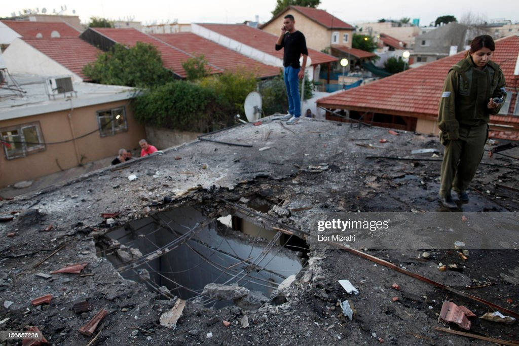 Israelis inspect the damage to a house that was hit by a rocket fired by Palestinian militants from the Gaza Strip on November 18 2012 in Ofakim...