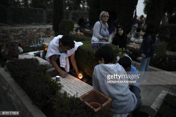 Israelis light candles at the graves of their loved ones at the Mount Herzel military cemetery in Jerusalem on April 30 at the start of Remembrance...