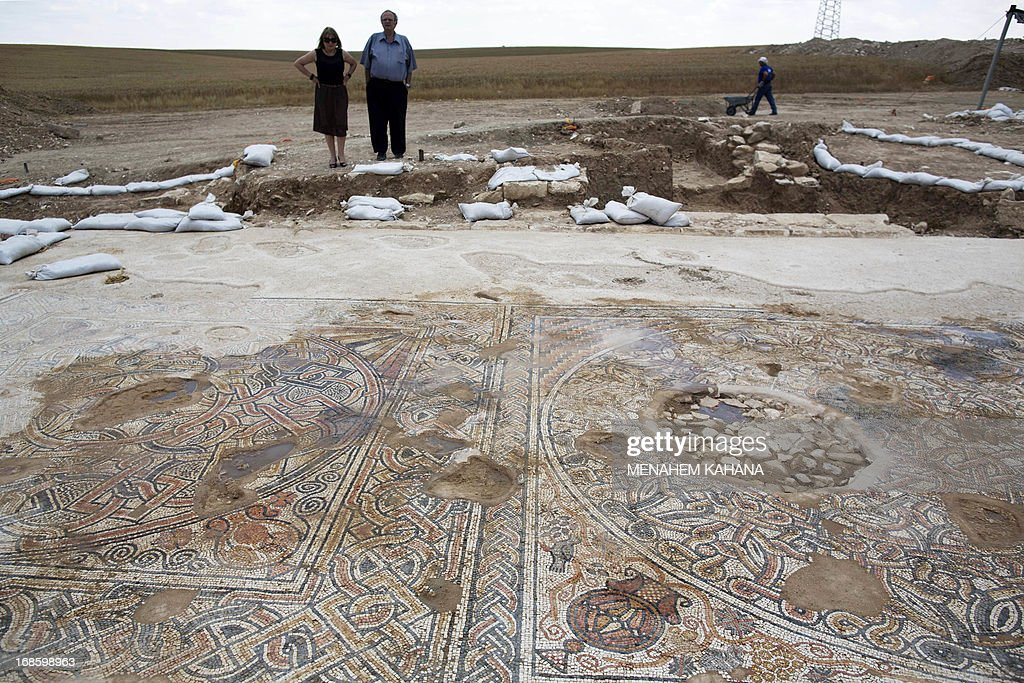 Israelis look at a 1500-year-old Byzantine era mosaic floor near Kibbutz Beit Kama in the Israeli Negev on May 12 2013. The mosaic dating back to the 4th-6th century BC was discovered along with a group of structures under the fields of the Kibbutz Beit before the imminent paving of the southern extension of Highway 6.