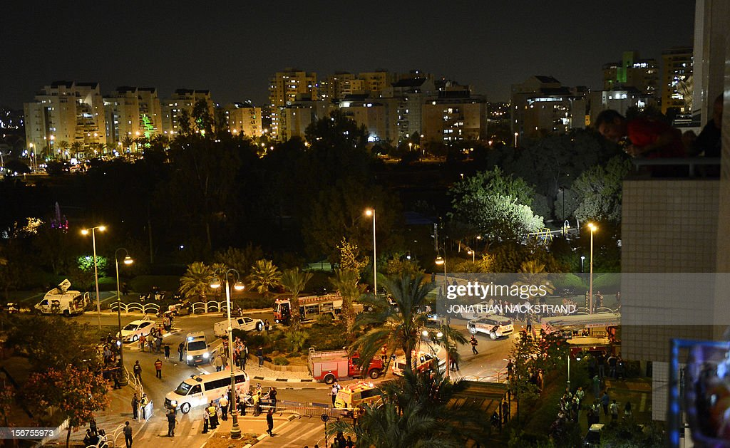 Israelis look on from their balcony as emergency services block the road leading to a destroyed building that was hit by a rocket, fired from Gaza, in the city of Rishon Letzion, near Tel Aviv, on November 20, 2012. Israeli Prime Minister Benjamin Netanyahu told Gaza's Hamas leaders to choose between peace and 'the sword' as a diplomatic push intensified to end a week of violence in and around the strip.