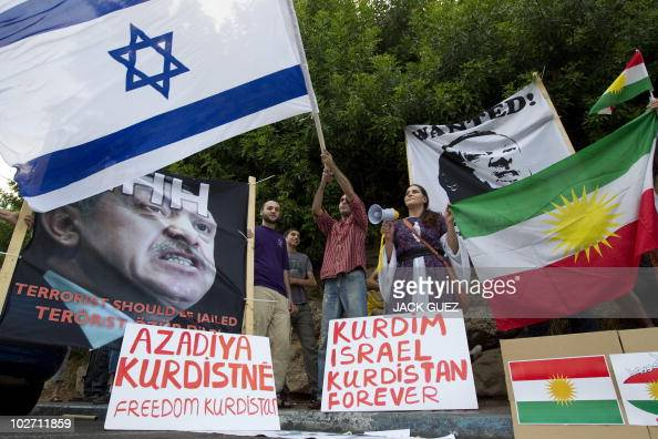 Israelis of Kurdish origin hold up Kurdish and Israeli flags as well portraits of Turkey's Prime Minister Recep Tayyip Erdogan whom they labelled a...