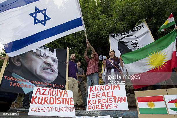 Israelis of Kurdish origin hold up Kurdish and Israeli flags as well portraits of Turkey's Prime Minister Recep Tayyip Erdogan whom they labelled a...