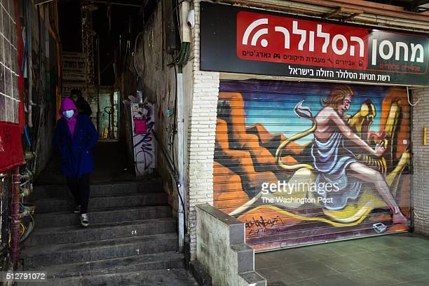 Israelis pass next to a graffiti depicting Samson killing a lion with his bare hands which was painted over a closed shutter at the Mahane Yehuda...