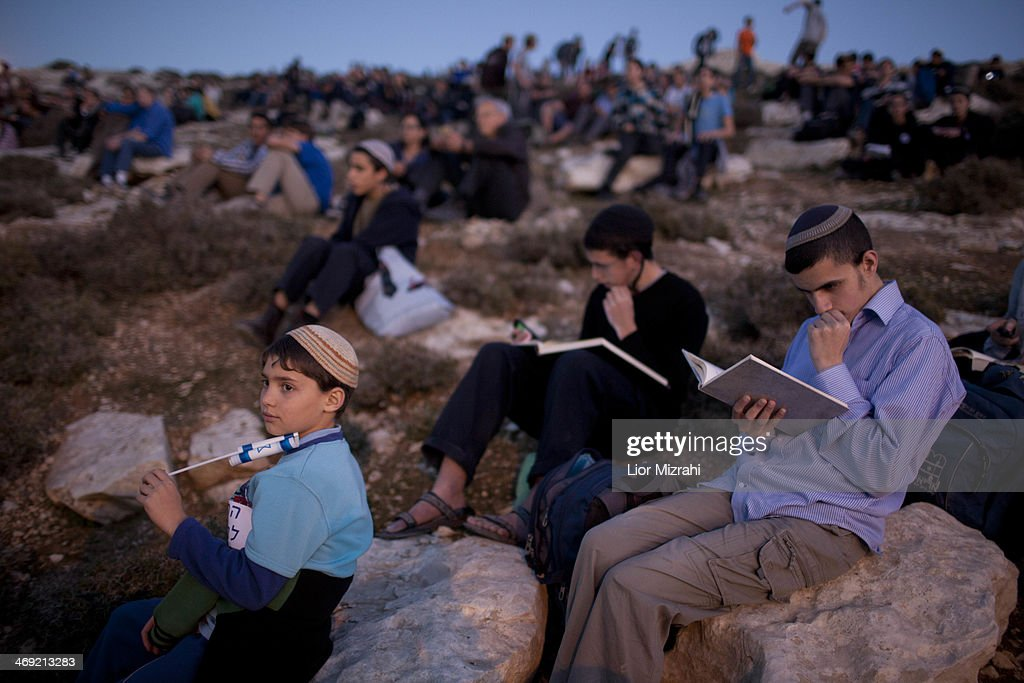 Israelis settlers and right wing activists pray after arriving at the area called E1 during a march from the Jewish settlement of Ma'ale Adumim February 13, 2014 at the Israeli settlement of Maale Adumimin , the West Bank. Israeli rightists and members of Israeli Prime Minister Benjamin Netanyahu's cabinet marched to the contested West Bank area, to protest at Netanyahu's decision to block construction there.