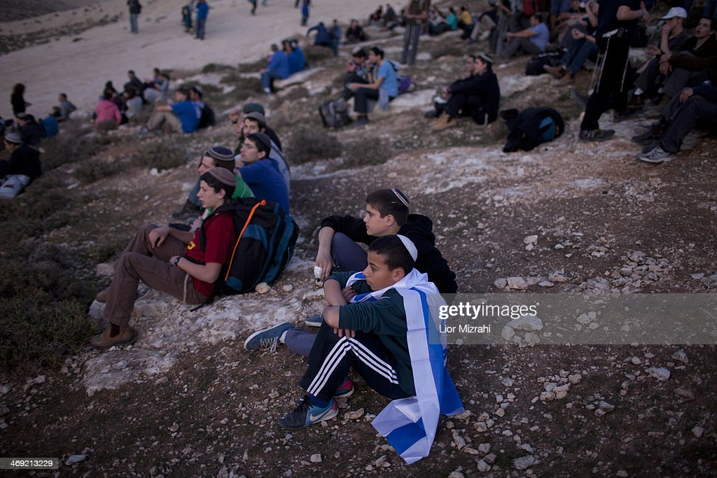 Israelis settlers and right wing activists sit after arriving at the area called E1 during a march from the Jewish settlement of Ma'ale Adumim February 13, 2014 at the Israeli settlement of Maale Adumimin , the West Bank. Israeli rightists and members of Israeli Prime Minister Benjamin Netanyahu's cabinet marched to the contested West Bank area, to protest at Netanyahu's decision to block construction there.