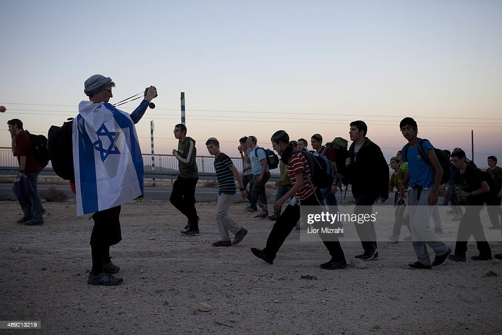 Israelis settlers and right wing activists walk up a road in the rural area known as E1 during a march from Ma'ale Adumimon February 13, 2014 at the Israeli settlement of Maale Adumimin , the West Bank. Israeli rightists and members of Israeli Prime Minister Benjamin Netanyahu's cabinet marched to the contested West Bank area, to protest at Netanyahu's decision to block construction there.