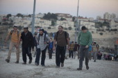 Israelis settlers and right wing activists walk up a road in the rural area known as E1 during a march from Ma'ale Adumimon February 13 2014 at the...