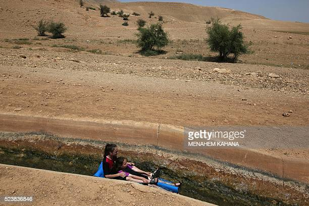 Israelis slide down a water canal in near the West Bank village of AlAuja in the Jordan Valley on April 24 2016 during the Jewish Passover holiday...
