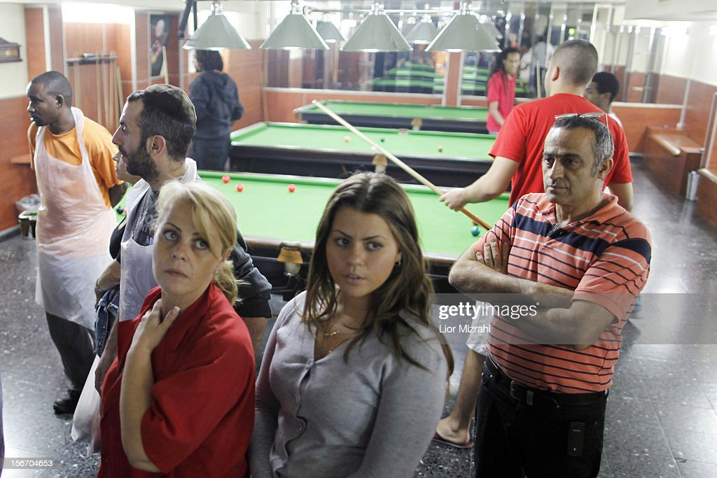 Israelis stand in a billiard room used as a shelter while air raid sirens sound November 19, 2012 in Ashdod, Israel. According to reports November 19, 2012, at least 90 Palestinians have been killed and more than 700 wounded during the Israeli offensive in the Gaza Strip.