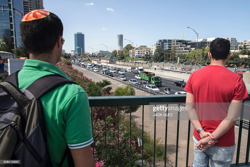 Israelis stop and stand in silence as they look towards a highway in the Israeli city of Tel Aviv on May 5, 2016, as sirens wailed across Israel for two minutes marking the annual day of remembrance for the six million Jewish victims of the Nazi genocide. Israel began marking Holocaust Martyrs and Heroes Remembrance Day at sundown on May 4 with a ceremony at the Yad Vashem memorial museum in Jerusalem, which commemorates the Jews killed by the Nazi regime during World War II. / AFP / JACK