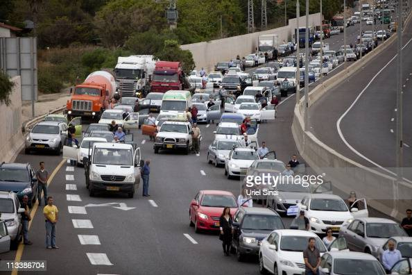 Israelis stop their vehicles and stand in silence beside them on the highway as sirens sound for two minutes across the country in memory of the...