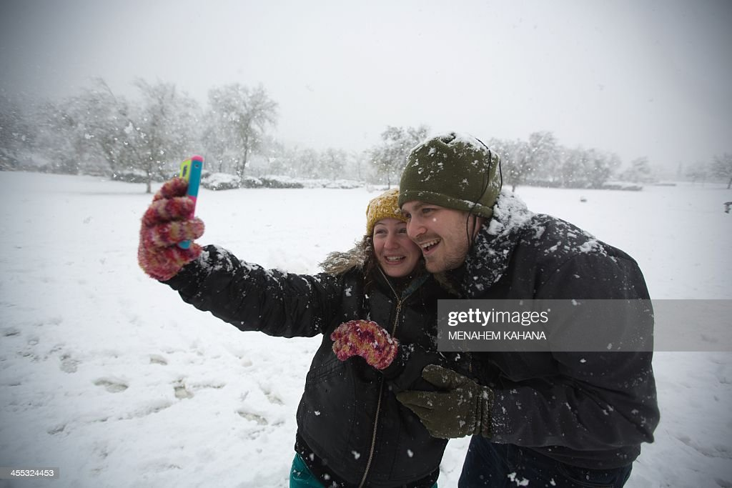 Israelis take a selfie in Jerusalem as snow falls on December 12, 2013. A bruising winter storm brought severe weather to the Middle East, forcing the closure of roads and schools and blanketing much of the high altitude areas with snow and ice. AFP PHOTO/MENAHEM KAHANA