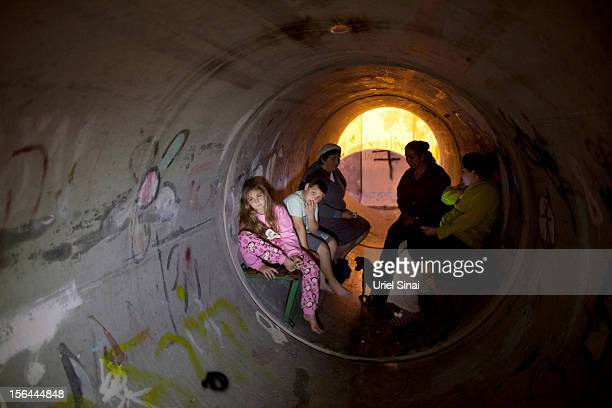Israelis take cover in a large concrete pipe used as a bomb shelter after a rocket was launched from the Gaza Strip on November 15 2012 in Nitzan...