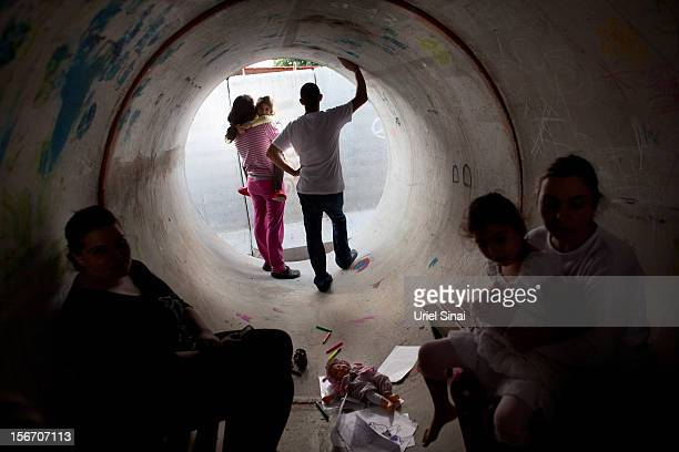 Israelis take cover in a large concrete pipe used as a bomb shelter during a rocket attack from the Gaza Strip on November 19 2012 in Nitzan Israel...