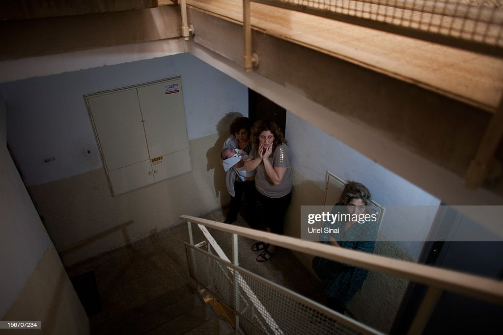 Israelis take cover in a stairway during a rocket attack from the Gaza Strip on November 19, 2012 in Ashkelon, Israel. According to reports November 19, 2012, at least 90 Palestinians have been killed and more than 700 wounded during the Israeli offensive in the Gaza Strip.
