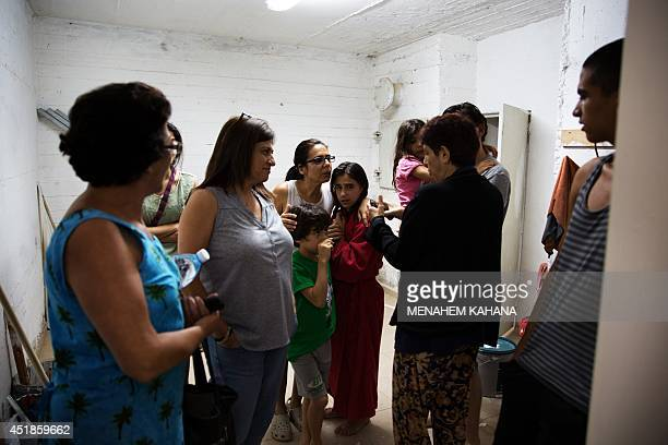 Israelis take cover in the shelter of a building in Jerusalem on July 8 2014 during a rocket attack by Palestinian militants from the nearby Gaza...