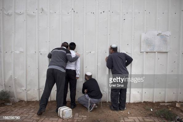 Israelis use holes in a fence to look into a factory after it was hit by a rocket launched from the Gaza Strip on November 12 2012 in Netivot Israel...