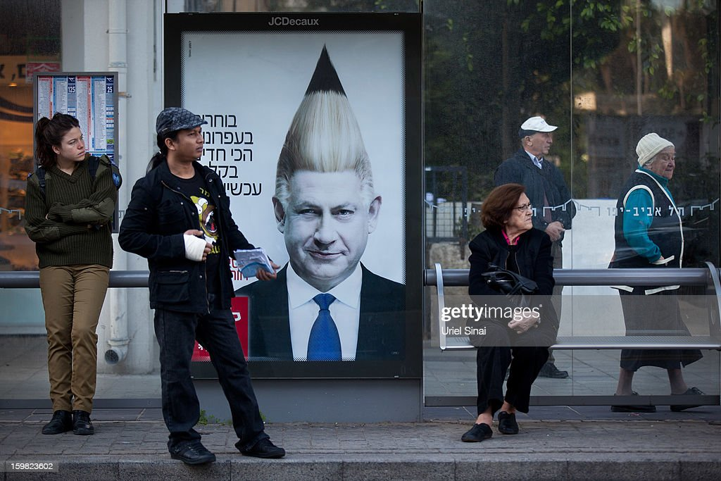 Israelis wait for the bus alongside a commercial poster for an Israeli school displaying the manipulated image of Israeli Prime Minister Benjamin Netanyahu hangs on a bus stop on January 21, 2013 in Tel Aviv, Israel. Israeli elections are scheduled for January 22 and so far showing a majority for the Israeli right.