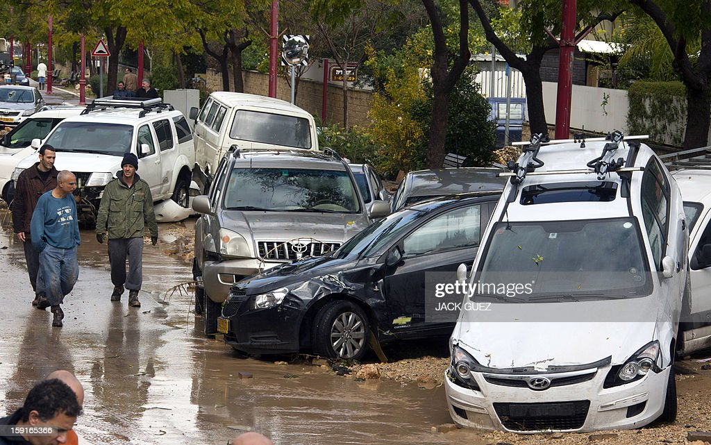 Israelis walk past damaged cars in Beit Hefer near the Meditrranean coastal city of Netanya, north of Tel Aviv, on January 9, 2013, after heavy rains overnight. Israel and the Palestinian territories have been lashed by heavy rain and high winds since January 6, which has caused flooding across the region.