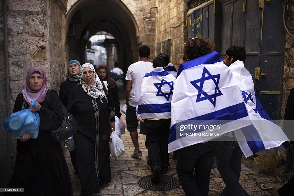 Israelis walk past Palestinian women as they march in the old city of Jerusalem on June 1 2011 during the Jerusalem Day parade in the city's mainly...